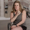 """A woman with an amputated led sits in a chair with the words, """"It is what it is,"""" on her arm."""