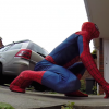 A man dressed up in a Spiderman costume on his hands and knees looking up at a smiling boy