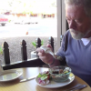 Man with spoon eats from bowl