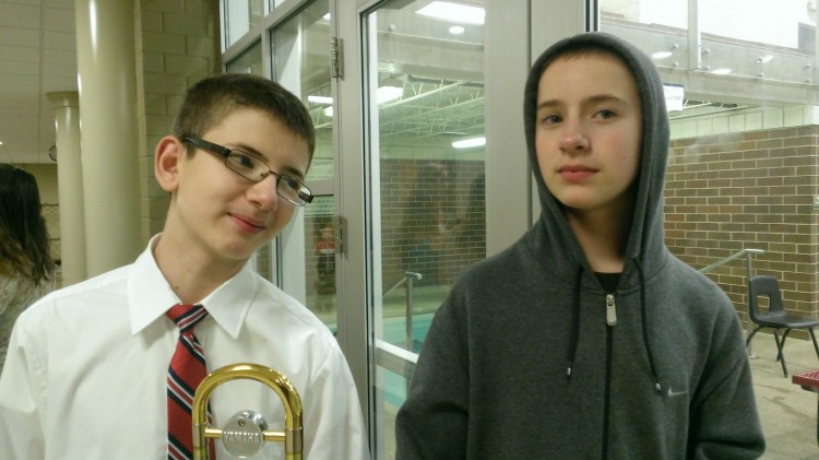 Two boys, one wearing a button-down shirt with a tie, the other wearing a hoodie with the hood on his head