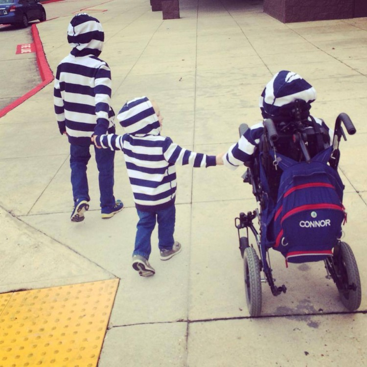 three brothers, one in wheelchair, all holding hands