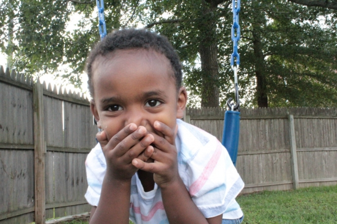 author's son smiles and covers mouth outside on a swing