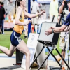 A young woman crossing the finish line of a race with her coach on the other side of the line, waiting to catch her.