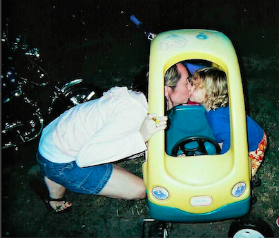 mother kisses son playing in toy car