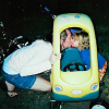 mother kisses son playing in a toy car