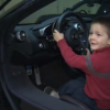 little boy sits behind the wheel of a car