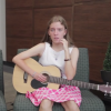 teen with cerebral palsy sits on a chair with her guitar