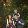 Family of four, mom, daughter, son and father, smile outdoors in front of trees