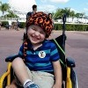 author's son sitting in his wheelchair and smiling