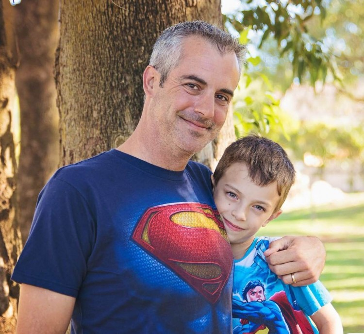 father and son in superman shirts hugging in park