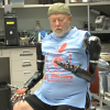 A double amputee, wearing a baseball cap and seated in a chair as he looks down at his prosthetic arms