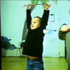 Two little boys holding sticks, one above his head and the other under his neck, as they stand in dance studio