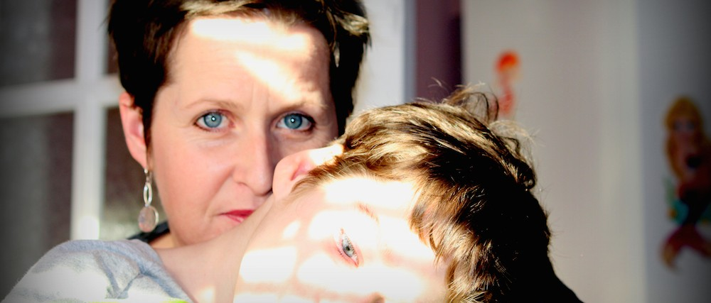 woman behind son who is resting his head on his arms