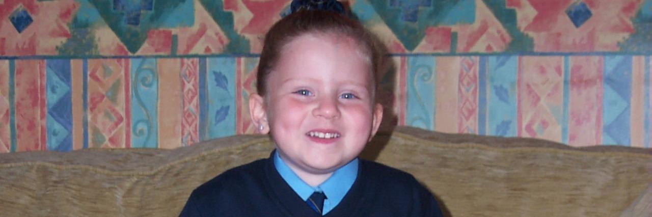 little girl in school uniform with walking aids