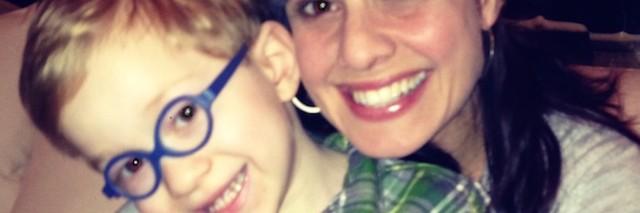 mom hugging toddler son in glasses