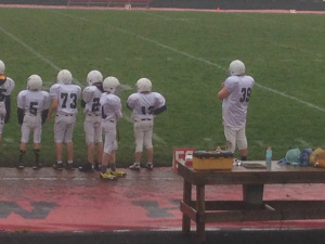group of football players and author's son standing outside the circle
