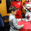 A small boy at a table with adults dressed in 'Star Wars' costumes standind around him