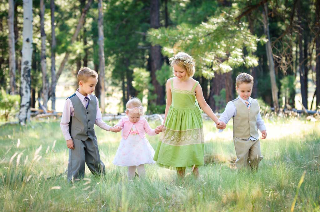 four children dressed up and holding hands in a field