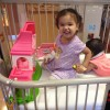 young girl playing and smiling in her crib