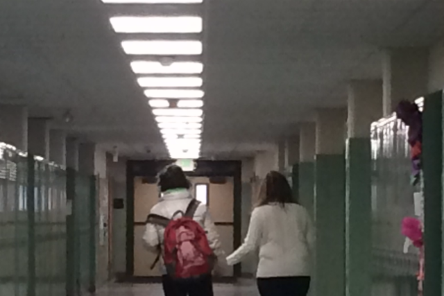 A woman holds a female students hand as she walks her to class