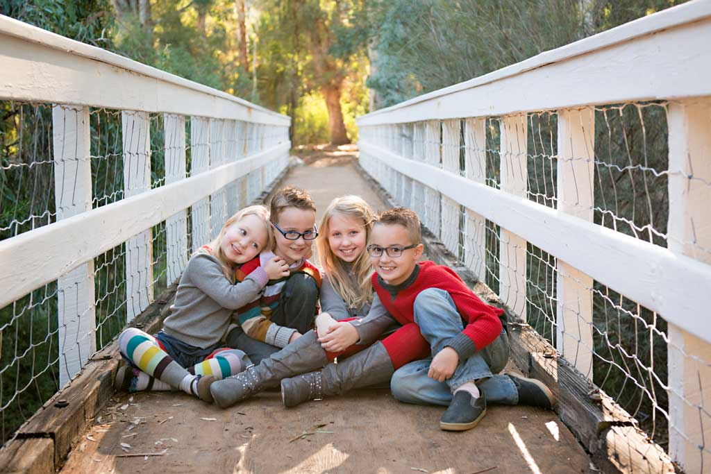 four children hugging outside on a bridge