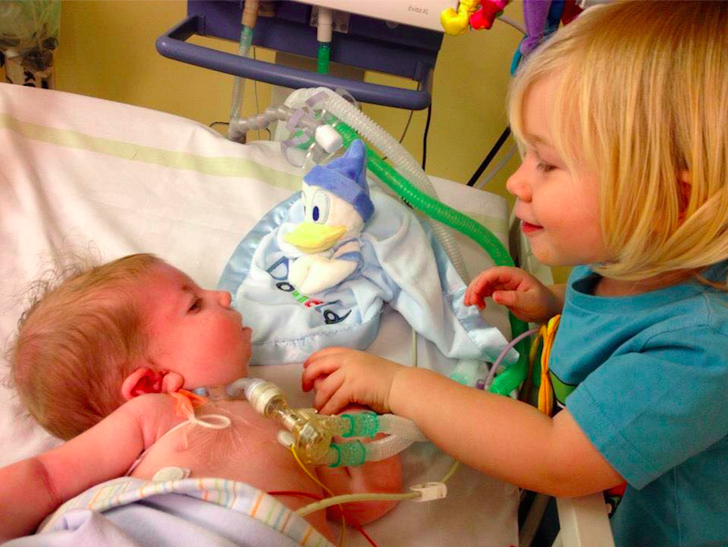 Natalie Lowndes sister looking over baby sibling with oxygen tubes and IVs