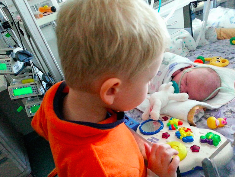brother looking at baby sibling in NICU