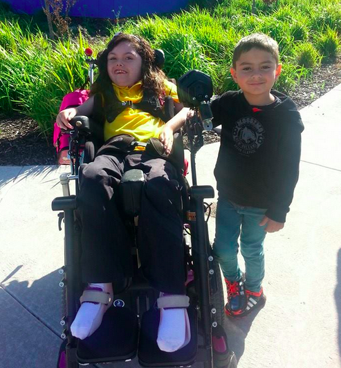 brother standing next to sister in wheelchair