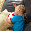 A small boy resting with a teddy bear and a soccer ball
