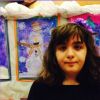 young girl standing in front of snowman paintings at school