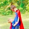 older brother in superman outfit holding hands of younger brother in cape