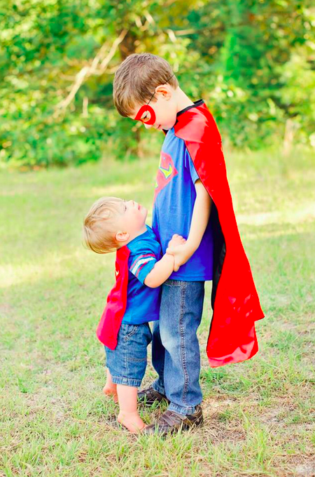 Photo credit Angela Reynolds Photography, big brother in superman cape holding little brother in cape