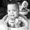 young boy smiling and sitting in a highchair