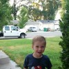 A boy in a Mario t-shirt smiles for camera as he stands on the sidewalk in front of his house