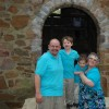 Fmaily of four standing in front of door opening, dad, two sons and mom