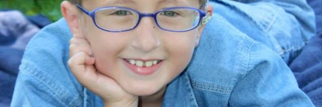 A boy with glasses with one hand on his cheek looking up and smiling into camera