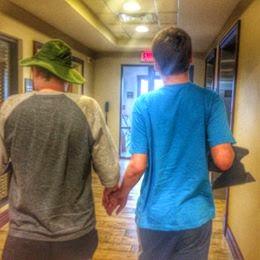 two friends holding hands walking in the hall