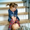 Young girl with Down syndrome smiling at her brother who is lying upside down on the stairs