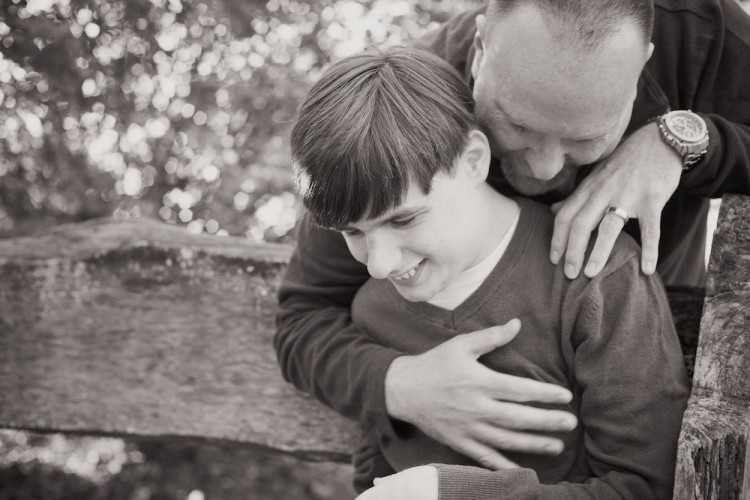black and white photo of father hugging son from behind