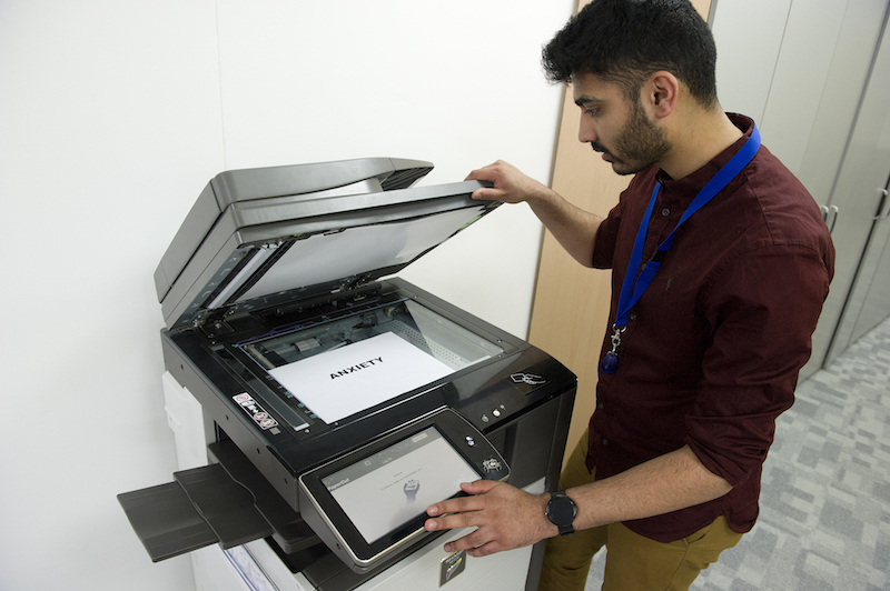 An office worker at a photocopier with a sign saying 'anxiety'.