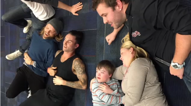 Adam Levine and Maroon 5 band lying on the floor with Christopher