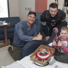 Chris Evans and Chris Pratt sitting smiling next to a boy in his hospital bed at Seattle Children's Hospital