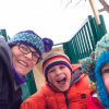 mom with two sons in winter clothes playing outside on a playground