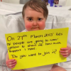 "An infant boy holds a yellow sign that says, ""On 27th March 2015 lots of people are going to wear yellow to show me how much support I have. Do you want to join in?"""