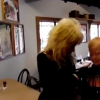 Dolly Parton, a blond woman, standing next to a teen boy with brown hair as he looks down at him