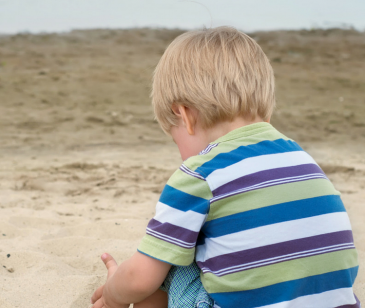 Boy in striped shirt sitting on the sand
