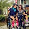 woman kneeling between two girls in wheelchairs