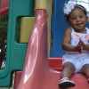 A small girl at the top of a slide on a playset