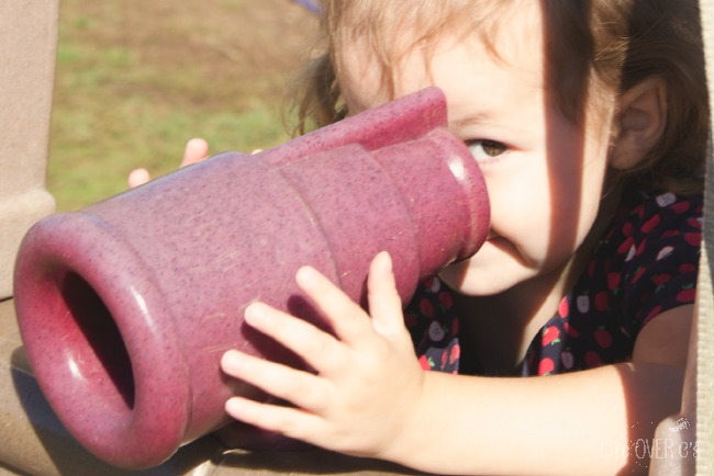 young girl looking through play telescope
