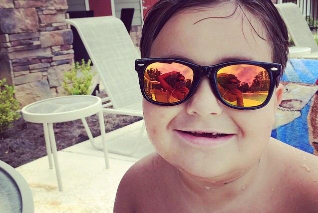 Boy wearing reflective sunglasses next to a pool